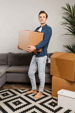 Man with cardboard box in hands on background of gray sofa, indoor plants.