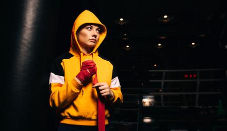 Sports girl boxer in yellow sweatshirt pulls red bandages on her hands. Banco de Imagens
