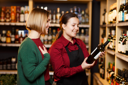 Image of seller and buyer on blurred background of racks with bottles of wine