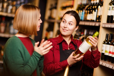 Photo of two young women with bottle in hands at liquor store Imagens