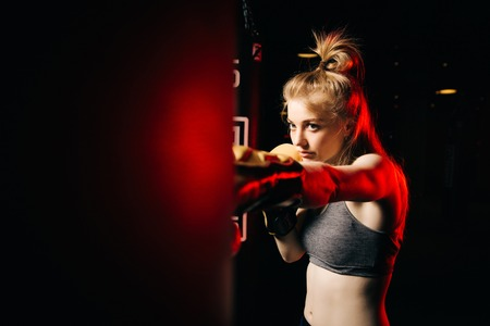 Blonde athlete woman in boxing gloves hits bag in training. Reklamní fotografie