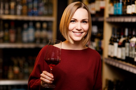 Picture of blonde with glass in hands at store with wine Imagens