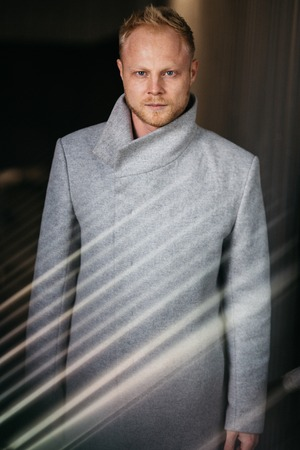 Photo of blond in gray coat on empty black background.