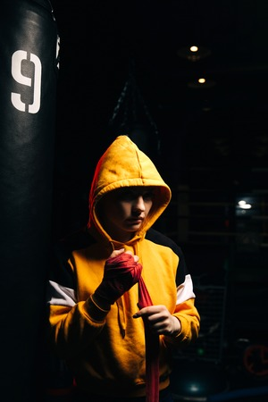 Sportive woman boxer in yellow sweatshirt pulls red bandages on her hands.