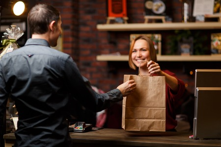 Photo of girl seller with paper bag and man shopper from back