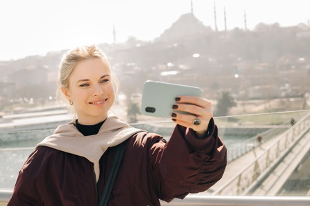 Young happy blonde in jacket makes selfie against background of glass window.