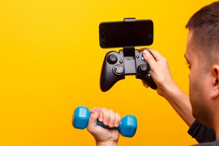 Image of mans hand with dumbbell and game console with smartphone. Reklamní fotografie