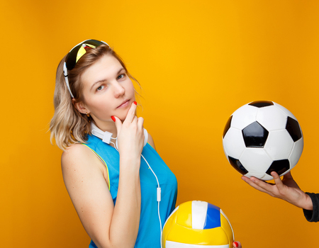 Sportswoman chooses between volleyball and soccer ball in studio .