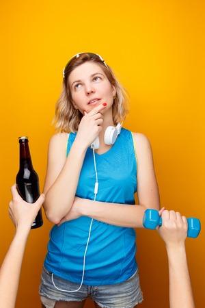 Thoughtful athletic girl in headphones before choosing dumbbell or beer bottle