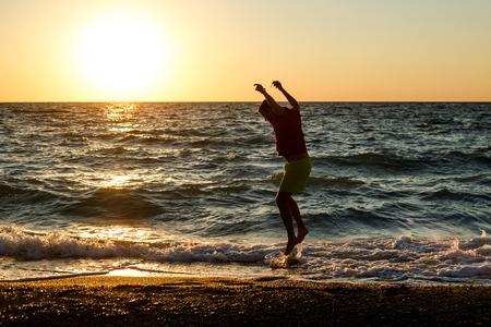 Foto eines glücklichen Mannes, der auf die Küste springt