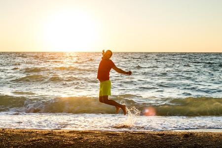 Bild eines glücklichen Mannes, der auf die Küste springt