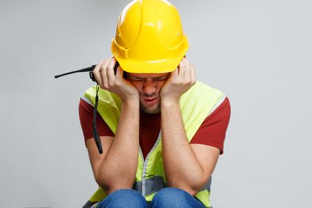 Photo of upset worker in yellow helmet with walkie talkie. Banco de Imagens