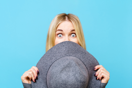 Photo of blonde covering her face with hat