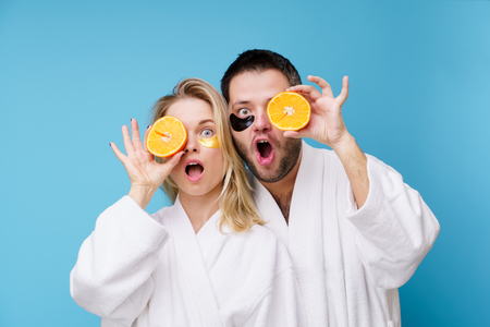Photo of man and woman with gel pads and oranges under eyes