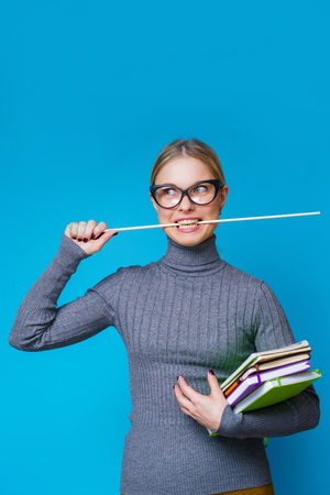 Photo of female teacher with pointer in her mouth and books