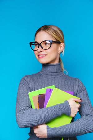 Photo of happy woman in glasses with books in hands