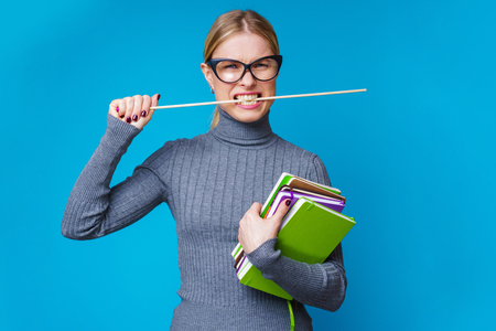 Image of female teacher with pointer in mouth with books in hands