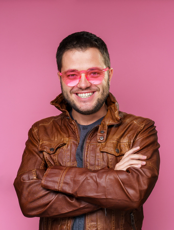 Image of happy brunet in pink glasses and leather jacket