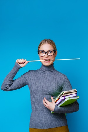 Portrait of woman teacher with pointer in her mouth and books
