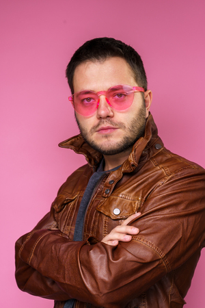 Photo of serious brunet man in pink glasses and leather jacket with arms crossed Stok Fotoğraf
