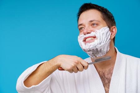 Photo of happy man in white coat shaving