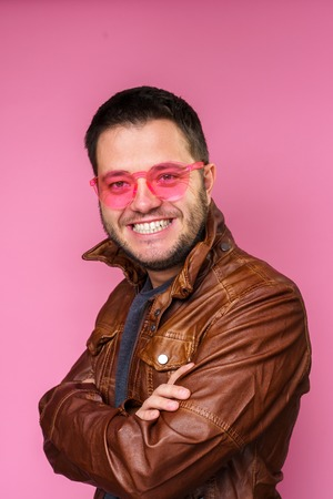 Photo of brunet man in pink glasses and leather jacket with arms crossed