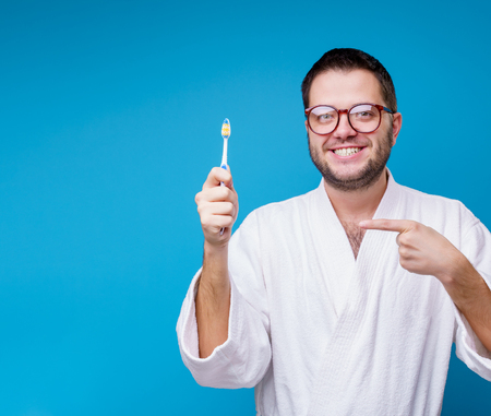 Photo of man with glasses in white coat with toothbrush in hands Stock Photo