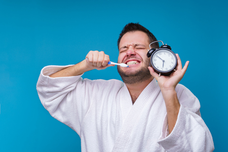 Photo of man with closed eyes with toothbrush and alarm clock in hands and in white coat