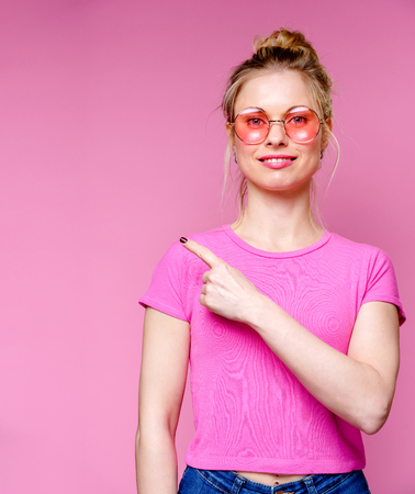 Image of smiling blonde in pink glasses pointing finger to side