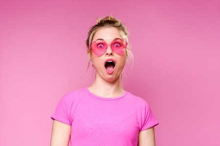 Photo of surprised blonde in pink T-shirt