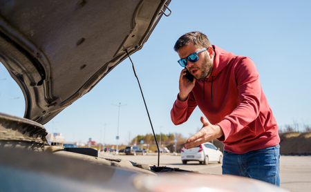 Photo of upset man with phone in next to open hood of broken car in daytime Stock Photo