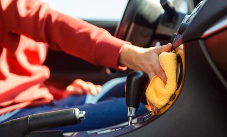Image of human hand with orange cloth washing car interior