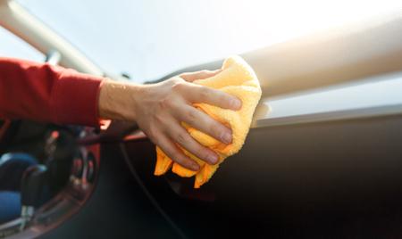 Photo of human hand with orange cloth washing machine interior, close-up.