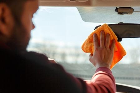 Photo from back of man with orange rag washing mirror of machine