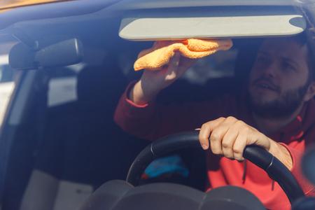 Photo of man with an orange rag washing windshield