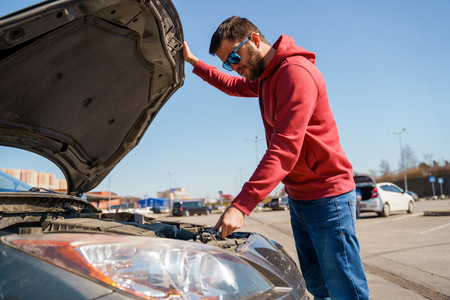 Photo of side of man with glasses next to open hood of broken car during day