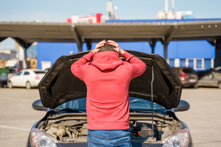 Photo on back of man next to open hood of broken car in daytime. Stock Photo