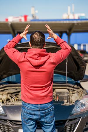Image on back of brunet man next to open hood of broken car in daytime outside