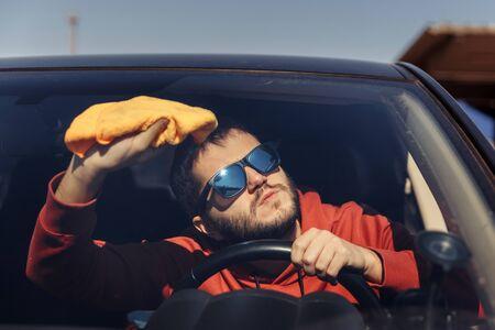 Photo of male with orange rag washing windshield