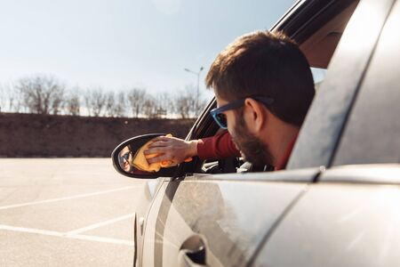 Image from back of man with orange rag washing distant-looking car mirror