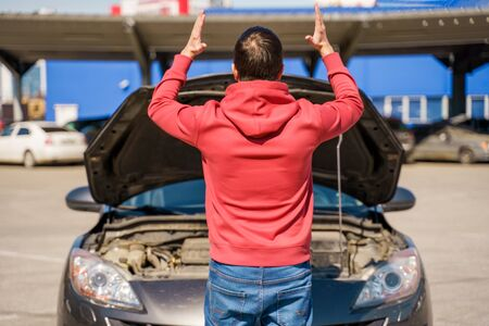 Image on back of man next to open hood of broken car in daytime Stok Fotoğraf