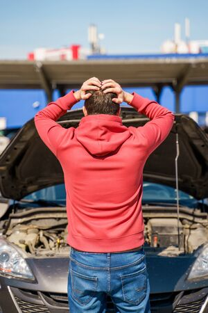 Image on back of male next to open hood of broken car in daytime Stock Photo