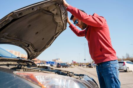 Image of side of man with glasses next to open hood of broken car during day