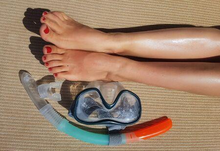 Photo of scuba, female legs on mat on summer