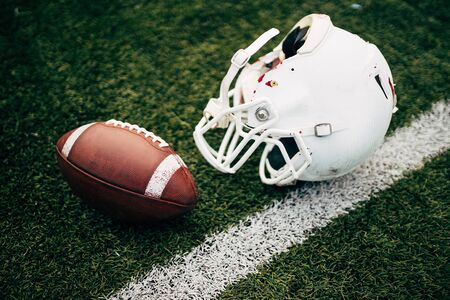 Photo of white helmet of Amerinian football player and ball on green lawn