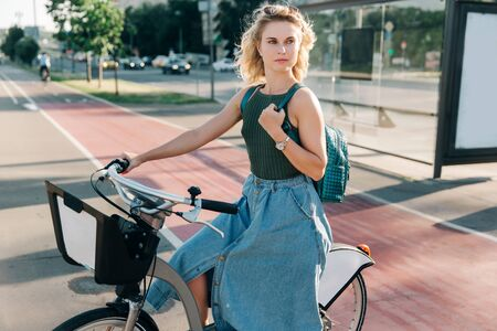 Photo of blonde woman sitting on bicycle near bus stop Zdjęcie Seryjne