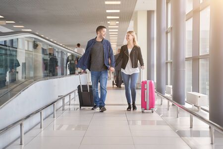 Photo of walking happy man and woman walking along walkway with suitcases at airport Archivio Fotografico