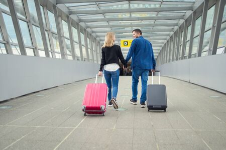 Photo from back of happy man and woman walking with suitcases at transition at airport Imagens