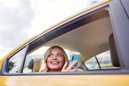 Photo of happy blonde looking at side with phone in her hand sitting in back seat in yellow taxi