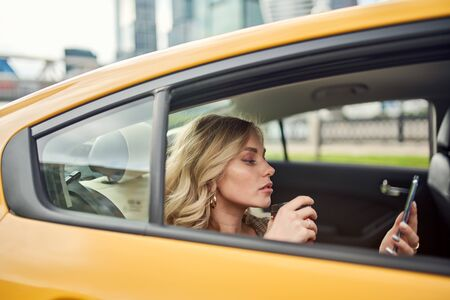 Side photo of blonde with glass and phone in her hands sitting in yellow car .